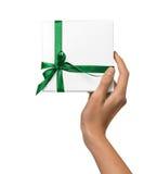 La femme d'isolement remet tenir le boîtier blanc actuel de vacances avec le ruban vert sur un fond blanc Images stock