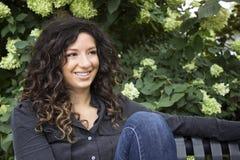 La femme d'une chevelure assez bouclée sourit dans la distance Photo libre de droits