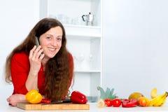 La femme d'une chevelure foncée dans la cuisine appelle Images stock