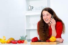 La femme d'une chevelure foncée dans la cuisine appelle Photo libre de droits