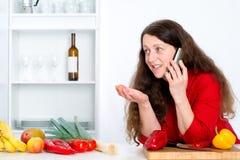 La femme d'une chevelure foncée dans la cuisine appelle Photo stock