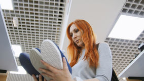La femme d'une chevelure rouge attirante choisit des espadrilles dans le magasin de chaussures - concept d'achats Photo libre de droits