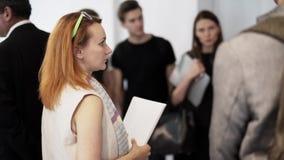La femme d'une chevelure rouge parle à d'autres jeunes à un certain événement banque de vidéos