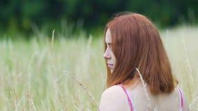 La femme d'une chevelure rouge regarde autour à la caméra dehors, belle dame de mouvement lent clips vidéos