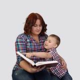 La femme d'une chevelure rouge s'assied ainsi que le petit garçon lisant un grand huent Image stock