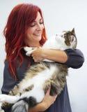 La femme d'une chevelure rouge sourit tout en tenant un grand chat de pure race image libre de droits
