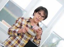 La femme d'une cinquantaine d'années boit la tasse de café Image libre de droits