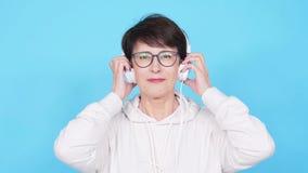 La femme d'une cinquantaine d'années dans les verres et un chandail blanc écoute sa musique préférée avec des écouteurs sur un fo clips vidéos