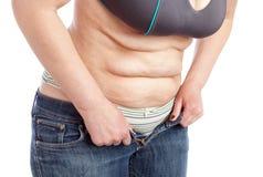 La femme d'une cinquantaine d'années montre le ventre avec l'excès de graisse. Images libres de droits
