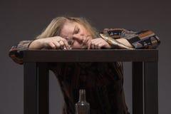 La femme d'une cinquantaine d'années seule boit un certains alcool de tristesse de vodka et e image stock
