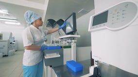 La femme dactylographie sur un moniteur, alors qu'un matériel médical fonctionne dans une salle de laboratoire 4K banque de vidéos