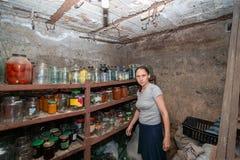 La femme dans la cave est aux cheveux gris, la fille prépare la nourriture pour l'hiver, nourriture en boîte dans des pots en ver images stock