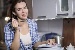La femme dans la cuisine prépare un repas Images stock