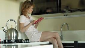 La femme dans des écouteurs dans la cuisine utilise le comprimé Matin banque de vidéos