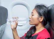 La femme dans des avions boit l'eau d'une bouteille en plastique Photographie stock