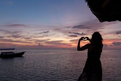La femme dans des cadres de lune de miel remettent dans la forme de coeur, cadre de coeur de doigt Coucher du soleil au-dessus de photographie stock libre de droits