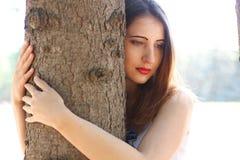 La femme dans des combinaisons se tient entre les troncs d'arbre Photographie stock