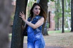 La femme dans des combinaisons se tient entre les troncs d'arbre Image stock