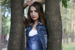 La femme dans des combinaisons se tient entre les troncs d'arbre Photos stock