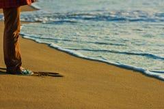 La femme dans des espadrilles est sur le sable Photographie stock libre de droits