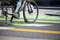 La femme dans des guêtres voyageant par la ville sur la bicyclette traverse la route au passage pour piétons photo libre de droits