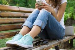 La femme dans des jeans s'assied sur un banc de parc et à l'aide d'un téléphone portable Photographie stock