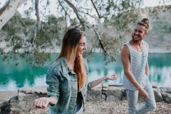La femme dans des jeans vêtx rire près de son ami en nature Photo libre de droits