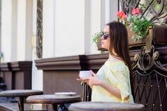 La femme dans des lunettes de soleil boivent du caf? dehors La fille d?tendent dans la tasse de cappuccino de caf? Dose de caf?in image libre de droits