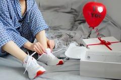 La femme dans des pyjamas attache les dentelles des chaussures sportives ` S D de Valentine Images libres de droits