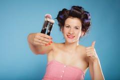 La femme dans des rouleaux de cheveux tient des brosses de maquillage Image libre de droits