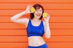 La femme dans des sports bleus portent des danses avec deux oranges et rires de tranche Concept sain frais de mode de vie photo stock