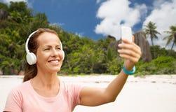 La femme dans des téléphones prend le selfie par le téléphone portable sur la plage images stock