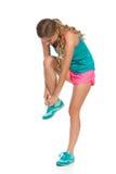 La femme dans des vêtements de sports attache sa chaussure Photo libre de droits