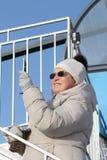 La femme dans des verres foncés photographiant le téléphone les roues d'un diable de carlingue Image libre de droits