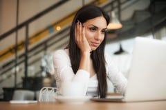 La femme dans l'amour boit le café et la causerie sur l'ordinateur portable Image stock