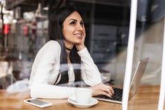 La femme dans l'amour boit le café et la causerie sur l'ordinateur portable Image libre de droits