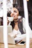 La femme dans l'amour boit le café et la causerie sur l'ordinateur portable Photo stock
