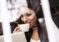 La femme dans l'amour boit le café et la causerie sur l'ordinateur portable Photo libre de droits