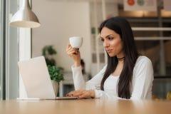 La femme dans l'amour boit le café et la causerie sur l'ordinateur portable Photos libres de droits