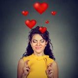 La femme dans l'amour faisant un souhait maintient ses doigts croisés Image libre de droits