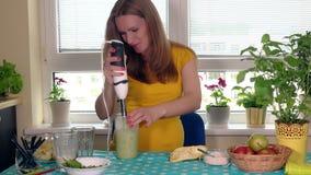 La femme dans l'expectative de sourire d'épouse de maison mélangent le cocktail de yaourt aux baies et aux fruits clips vidéos