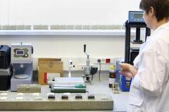 La femme dans l'habillement blanc travaille dans le laboratoire Photographie stock