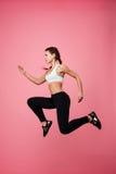 La femme dans l'habillement de sport feint le fonctionnement en air sautant haut photos libres de droits