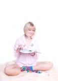 La femme dans la bande colorée mange afficher un livre Image stock