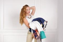 La femme dans la boutique choisissent les vêtements pour essayer photo stock