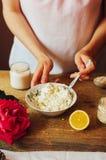 La femme dans la cuisine prépare le pudding de lait caillé bourré de Photographie stock libre de droits