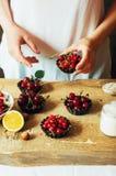 La femme dans la cuisine prépare le pudding de lait caillé bourré de Photographie stock