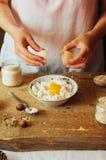 La femme dans la cuisine prépare le pudding de lait caillé bourré de Images libres de droits