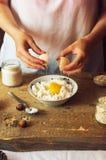 La femme dans la cuisine prépare le pudding de lait caillé bourré de Image libre de droits