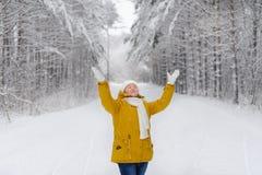 La femme dans la forêt d'hiver se réjouit dans la neige Photo libre de droits